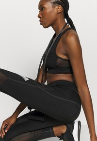 Puma - PAMELA  REIF X PUMA  COLLECTION LAYER SPORT CROP  - Medium support sports bra - black - 4