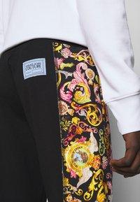 Versace Jeans Couture - HEAVY PRINT VERSAILLES - Tracksuit bottoms - black - 3