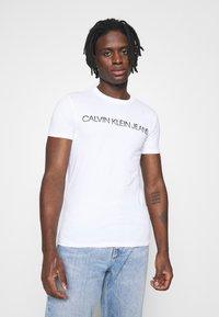 Calvin Klein Jeans - MIXED TECHNIQUE INSTIT LOGO TEE UNISEX - T-shirt con stampa - bright white - 0