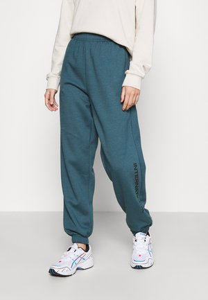 INTERNATIONAL SLOGAN JOGGER - Tracksuit bottoms - teal