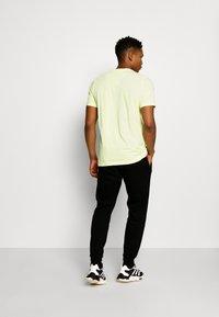 adidas Originals - COLLEGIATE CREST UNISEX - Tracksuit bottoms - black - 2