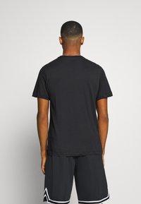 Nike Performance - DRY MEDALLION TEE - Print T-shirt - black - 2