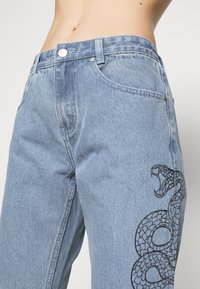 Milk it - SIDE SEAM SNAKE PRINT - Flared Jeans - light blue - 3