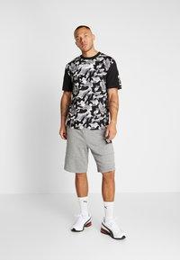 Puma - REBEL CAMO TEE - Print T-shirt - black - 1