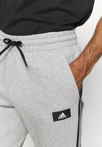 adidas Performance - 3 STRIPES FUTURE - Tracksuit bottoms - medium grey heather - 5