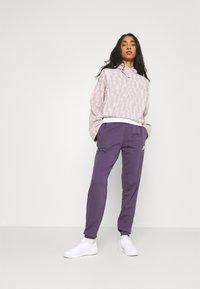 Nike Sportswear - Tracksuit bottoms - dark raisin/white - 1