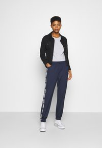 Tommy Jeans - JOGGER TAPE RELAXED - Tracksuit bottoms - twilight navy - 1