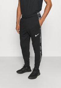 Nike Performance - CAMO - Tracksuit bottoms - black/white - 0