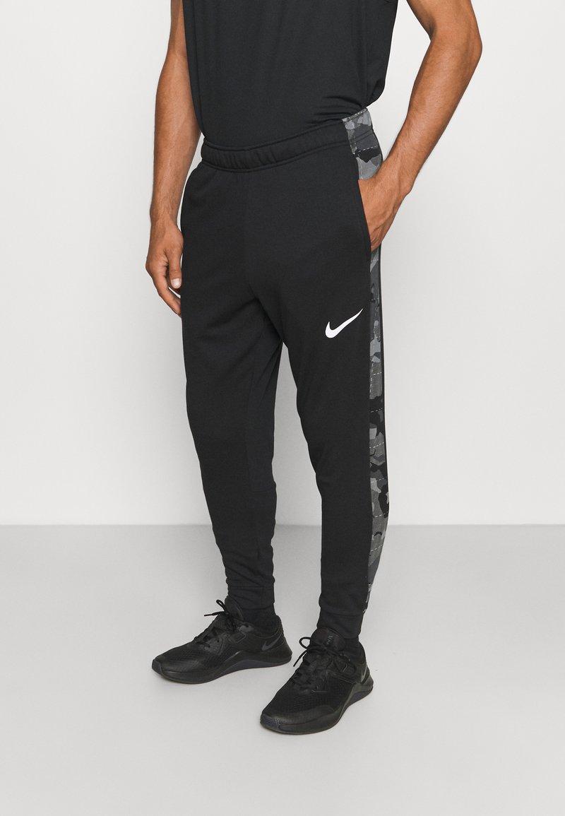 Nike Performance - CAMO - Tracksuit bottoms - black/white