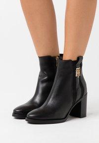 Tommy Hilfiger - INTERLOCK BOOT - Kotníková obuv na vysokém podpatku - black - 0