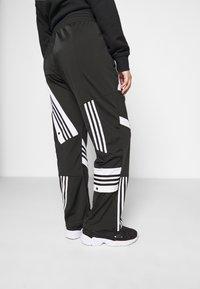 adidas Originals - CATHARI - Tracksuit bottoms - black - 4