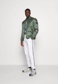 Calvin Klein - ESSENTIAL LOGO TAPE  - Tracksuit bottoms - bright white - 1