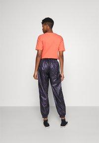 Nike Sportswear - Tracksuit bottoms - dark raisin/bright mango - 2