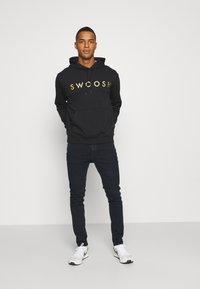 Nike Sportswear - HOODIE - Hoodie - black/gold - 1
