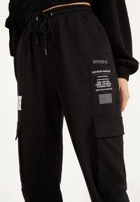 Bershka - IM CARGOSTIL AUS PLÜSCHGEWEBE  - Teplákové kalhoty - black - 3