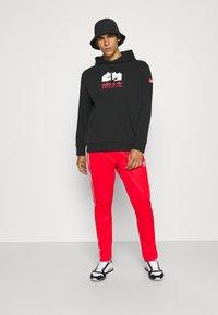adidas Originals - BECKENBAUER UNISEX - Tracksuit bottoms - red - 1