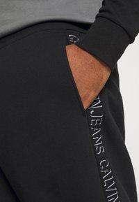 Calvin Klein Jeans Plus - SHADOW LOGO TAPE PANT - Verryttelyhousut - black - 4