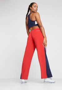 Tommy Sport - FLAG TAPE PANT FLARE - Träningsbyxor - red - 2