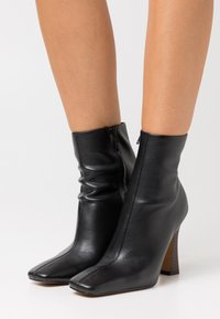 NA-KD - FLARED BOOTS - Enkellaarsjes met hoge hak - black - 0