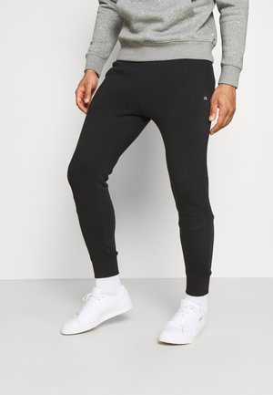 PLANET - Tracksuit bottoms - black