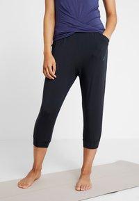Curare Yogawear - PANTS LONG LOOSE - Pantalon de survêtement - black - 0