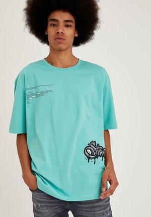 OVERSIZED - T-shirt med print - turquoise