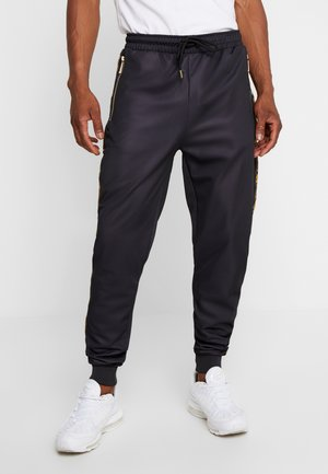 TRACK JOGGER - Tracksuit bottoms - black/gold
