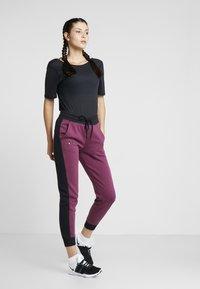 Under Armour - RIVAL GRAPHIC NOVELTY PANT - Spodnie treningowe - level purple/black - 1