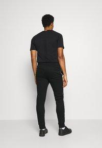 Champion - CUFF PANTS - Teplákové kalhoty - black - 2