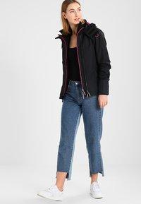 Superdry - TECH HOOD POP ZIP WINDCHEATER - Summer jacket - black/raspberry - 1