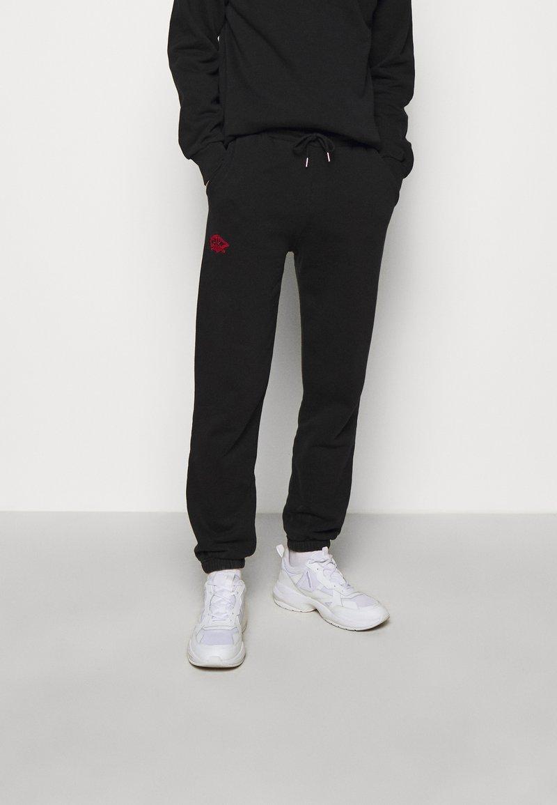 Han Kjøbenhavn - Tracksuit bottoms - faded black/red