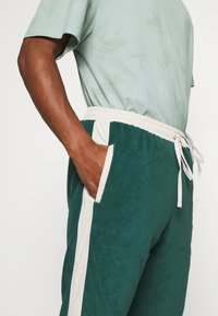 WRSTBHVR - TRACKPANTS LOUNGIN - Tracksuit bottoms - green/off white - 4