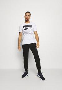 Puma - AMPLIFIED PANTS - Pantalon de survêtement - black - 1