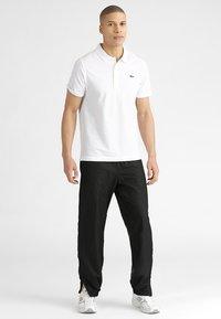 Lacoste Sport - TENNIS PANT - Pantalon de survêtement - black - 1