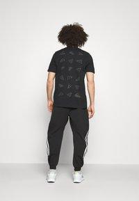 adidas Performance - 3-STRIPES O-PANT FUTURE ICONS - Tracksuit bottoms - black - 2