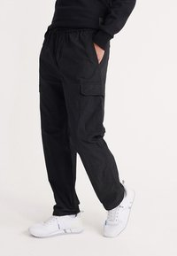 Superdry - UPERDRY NYCO PANTS - Cargo trousers - black - 0