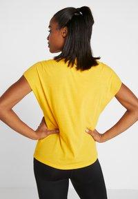 Nike Performance - DRY SIDE TIE  - T-shirt z nadrukiem - university gold/white - 2