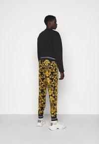 Versace Jeans Couture - TECNO  PRINT LOGO BAROQU  - Tracksuit bottoms - black - 2
