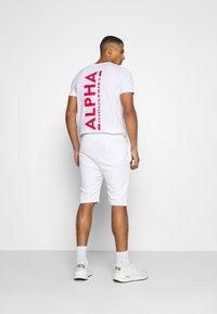 Alpha Industries - BASIC FOIL PRINT - Pantalon de survêtement - white/yellow gold - 2