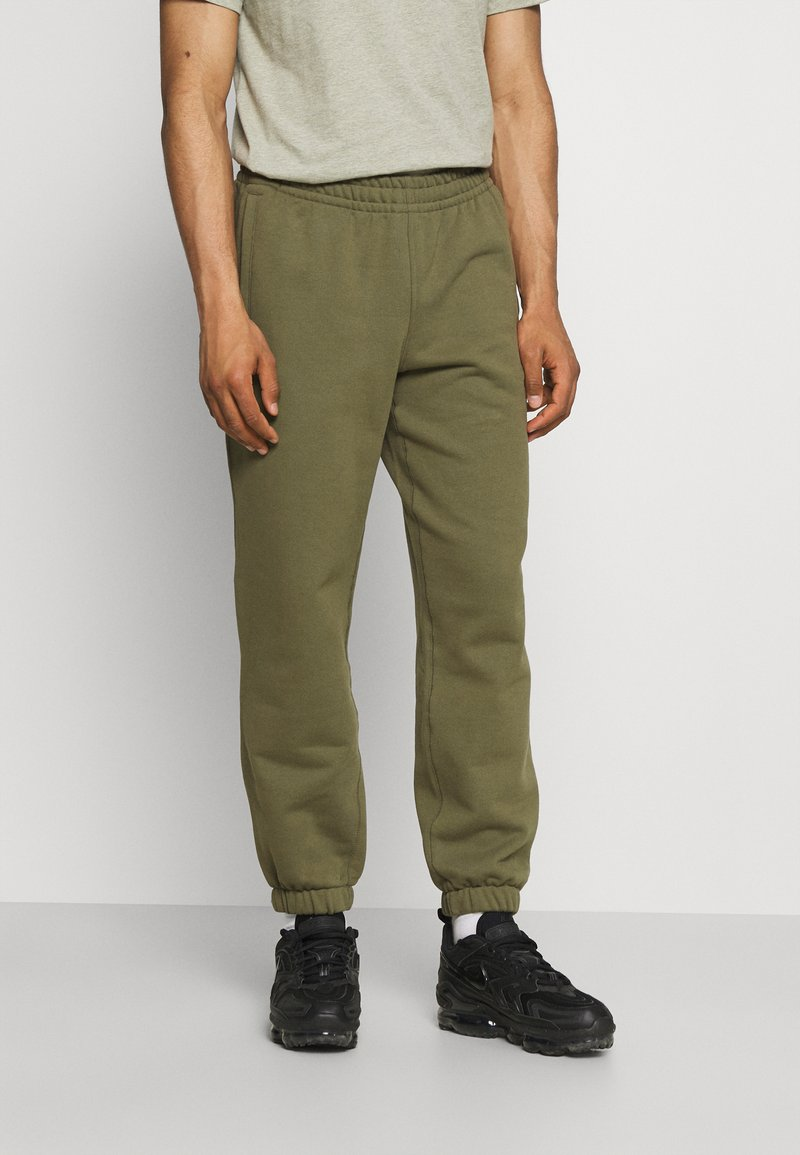 adidas Originals - BASICS UNISEX - Spodnie treningowe - olive cargo