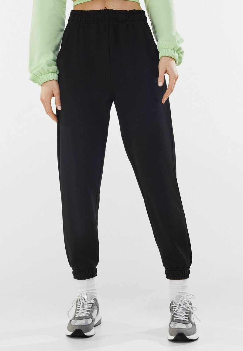 Bershka - Tracksuit bottoms - black