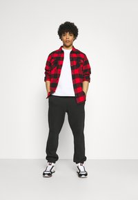 adidas Originals - BASICS UNISEX - Tracksuit bottoms - black - 1