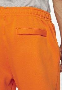 Nike Sportswear - CLUB - Tracksuit bottoms - magma orange/white - 4