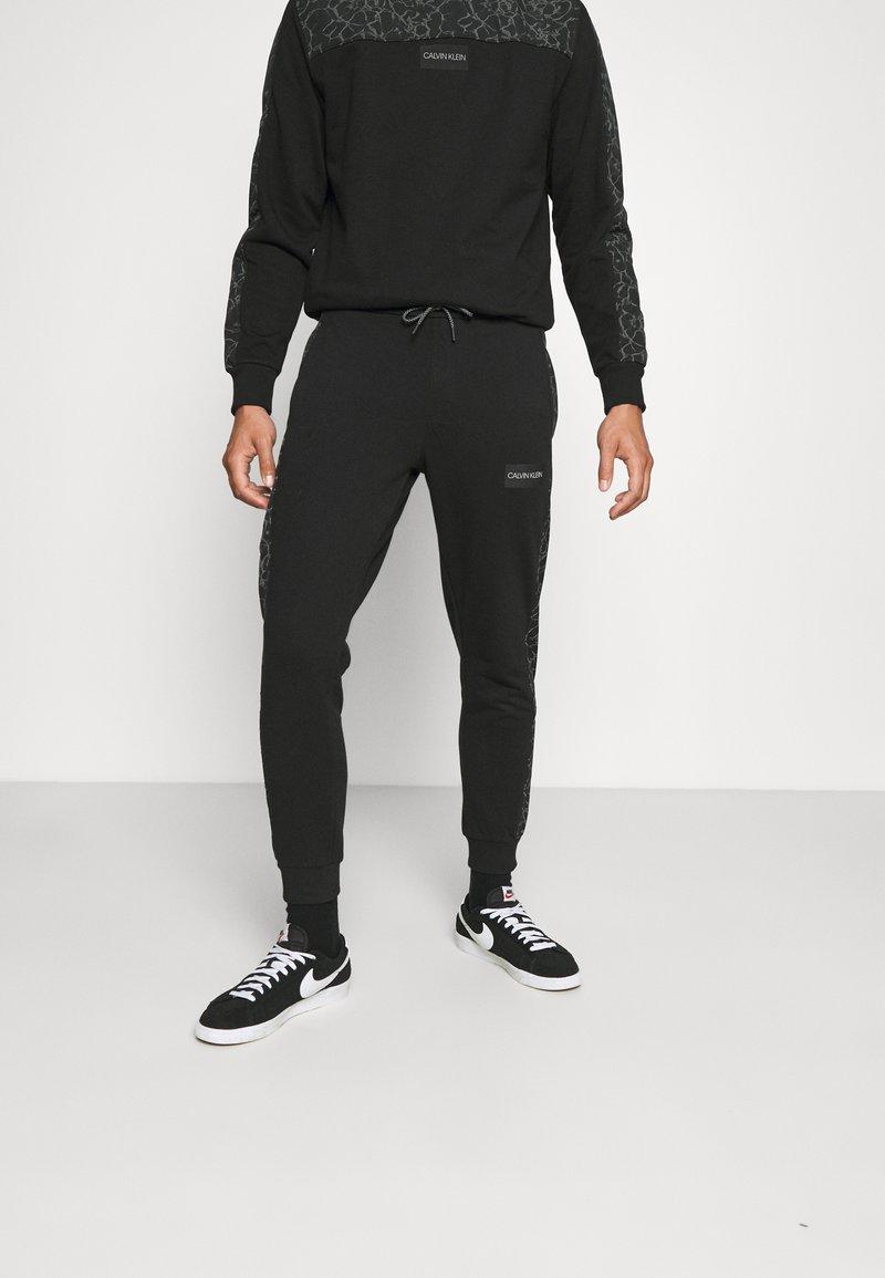 Calvin Klein - REFLECTIVE PRINT - Pantaloni sportivi - black
