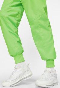 Nike Sportswear - Tracksuit bottoms - green strike/vapour green/white - 4