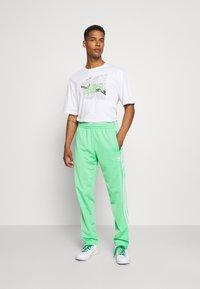 adidas Originals - FIREBIRD UNISEX - Spodnie treningowe - semi screaming green - 1