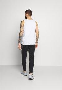 Nike Performance - TAPER - Tracksuit bottoms - black/white - 2