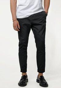 Tigha - Trousers - black - 0
