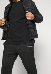 9N1M SENSE - LOGO PANTS UNISEX - Pantalon de survêtement - black - 3