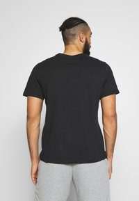 Nike Performance - DRY TEE - T-shirt med print - black/university red - 2